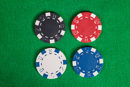 wagers: Four macro colorful poker chips on green table