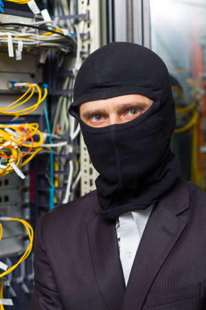 routing: robber in black mask hack server room downloading data on laptop Stock Photo