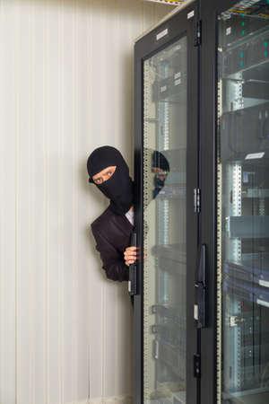 robber in black mask hack server room downloading data on laptop Stock Photo