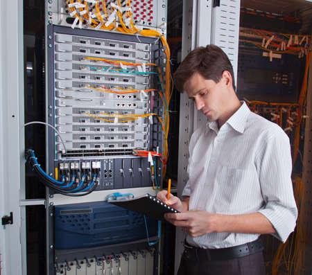 Network engineer in serverruimte met pen en tablet Stockfoto