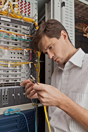 debugging: Network engineer in server room with optical patchcord