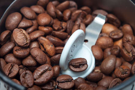 Macro electric coffee-mill machine with roasted coffee beans on isolate background photo