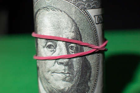tightened: one hundred Dollar roll tightened with red rubber band. . Green black background. Franklin looks at you. Stock Photo