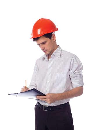Man in a shirt orange construction helmet writes black folder photo