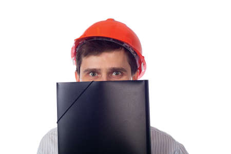 Man in a shirt orange construction helmet covers his face photo