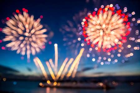fuegos artificiales: Fuera de foco coloridos fuegos artificiales en el cielo de fondo negro sobre el agua Foto de archivo
