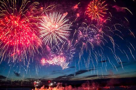 fireworks: coloridos fuegos artificiales en el cielo de fondo negro sobre el agua Foto de archivo