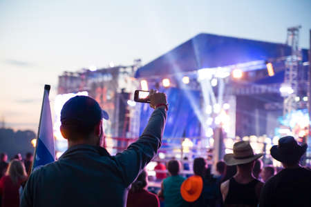 fans: silhouette of young man taking pictures rock concert on the phone open fest Stock Photo