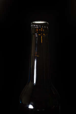 backgraound: Neck of a bottle of beer in the shade, black backgraound