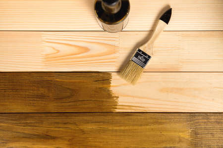 Process of painting the wood boards with the brush and the bottle with brown paint Standard-Bild
