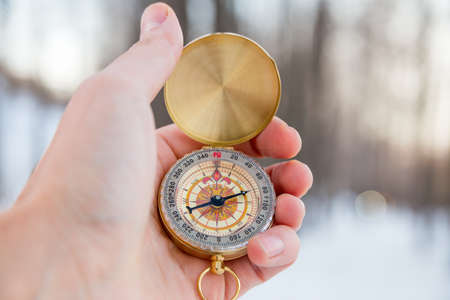Concept - orienteering in the woods, a route compass. Winter, a man holds a compass in hand Standard-Bild