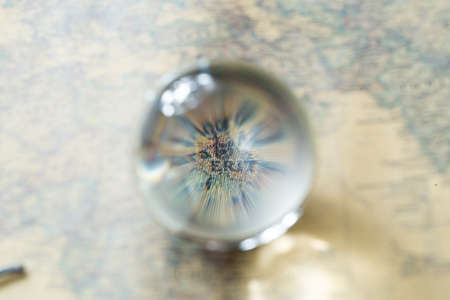 The glass sphere on old vintage map, macro background, Image inside ball in focus Standard-Bild