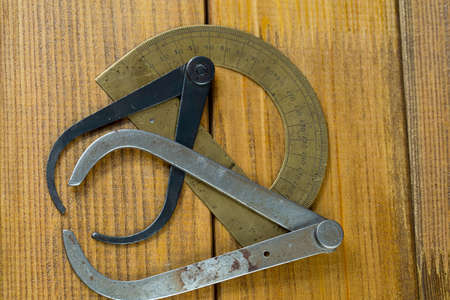 The protractor and two old calipers. Brown plywood background