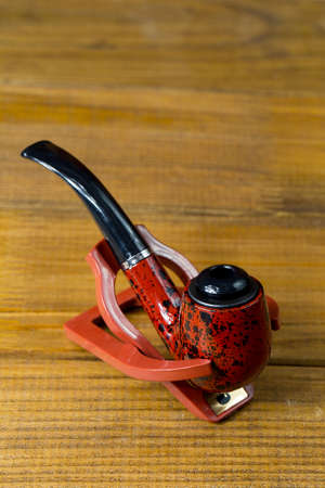 red-black classic tobacco pipe on a stand,  brown wooden backgro