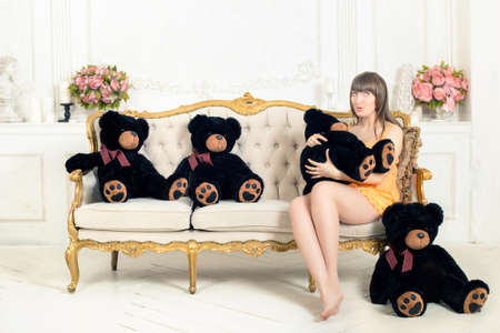 the Surprised young woman on the couch - in the hands many black teddy bears in old-fashioned style room