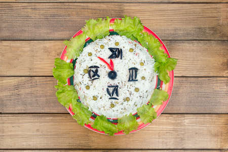 The Christmas salad rice olives greens peas - concept New year clock face, midnight, brown wooden background.