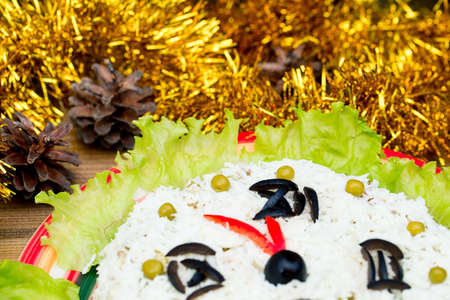 The Christmas salad rice olives greens peas - concept New year clock face, midnight, background spruce cones tinsel on the table.