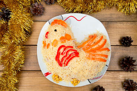 Christmas salad on plate - concept New year symbol rooster, background spruce cones tinsel the table. Standard-Bild