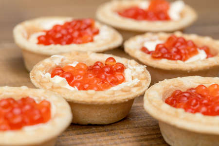 The Several tartlets with red caviar and butter on wooden brown table macro