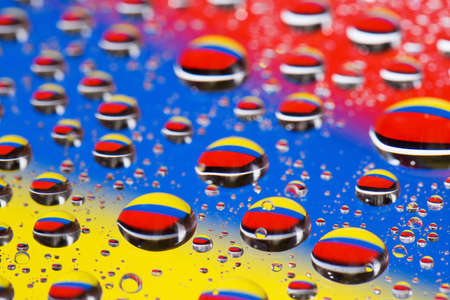 the Abstract blue-yellow-red background of water drops on glass with reflection green macro