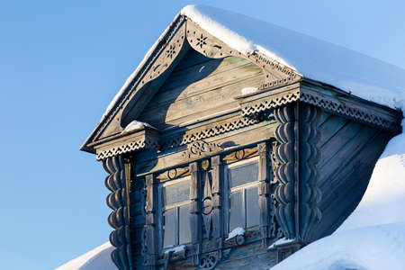 the Carved Window of an old country house in the snow against a blue sky background Standard-Bild