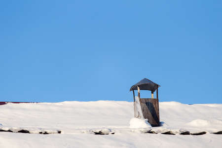 the Chimney and roof with snow against the blue sky