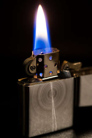 gas lighter: the macro metal lighter petrol On black background, open fire
