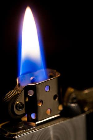 the macro metal lighter petrol On black background, open fire