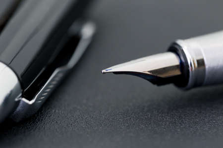 The black pen with a cap on a black background, business concept
