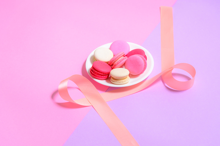 Homemade Colorful macaroons or macaron on White plate with copyspace on pink and purple background