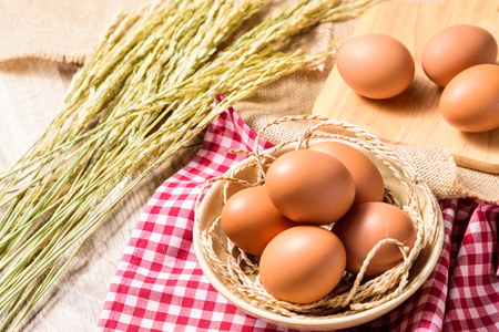 The eggs are placed in a white bowl and placed on a red Scottish plaid with ear of rice or spike