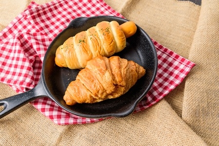 The homemade Croissant and Sausage bread is placed on a black plate shaped like a pan. and Placed on a red Scottish tablecloth and sack Banque d'images