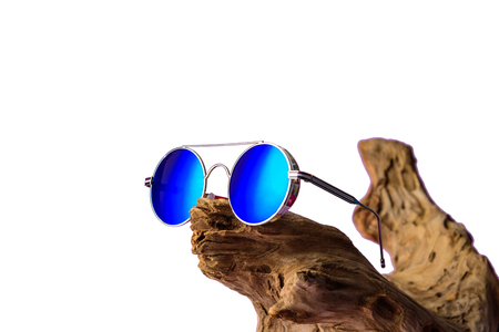 Fashionable sunglasses with blue lenses placed on timber. on white backgound or isolated