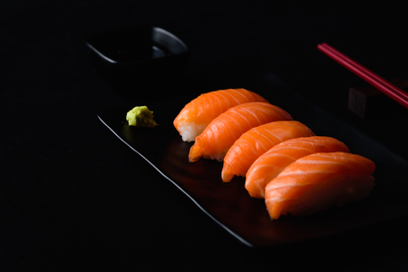 Salmon sushi with green wasabi on Black plate or dish and shoyu sauce on black background 版權商用圖片