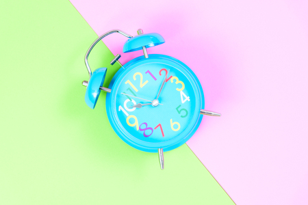 Blue Alarm clock on pink and green pastel background or isolated