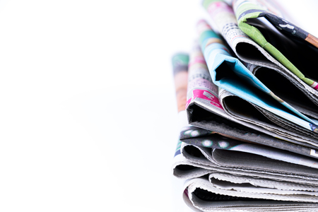 Close up of Colorful newspapers folded and stacked isolated on white background