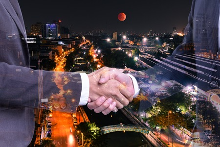 Concept business :  Double exposure of businessman making handshake with background of night bangkpk cityscapes with super blood moon Archivio Fotografico