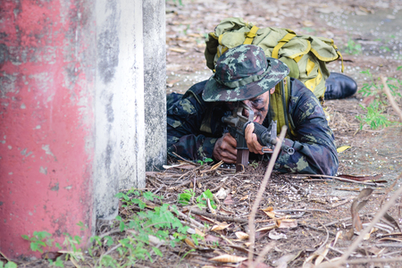 Bangkok Thailand - April  21 , 2018 :  Simulation of the battle plan. The soldiers or military squat on the grass and holding a machine gun  for ambush the enemy.