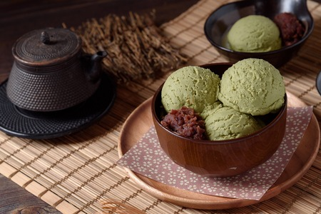 Top view of Homemade green tea or matcha ice cream in the wooden bowl with sweet red bean and put on bamboo mat
