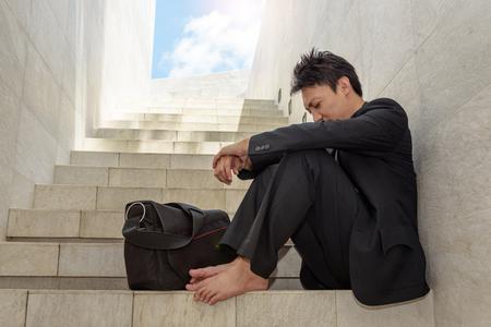 Concepto de fracaso empresarial: Jóvenes empresarios se sientan en las escaleras y con las manos entrelazadas las rodillas porque está tan desesperado, estresado, triste tras conocer la mala noticia de que está desempleado. Foto de archivo