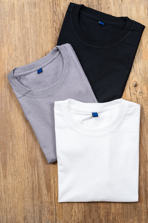 Colorato di t-shirt in cotone su fondo in legno. Archivio Fotografico