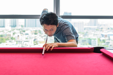 Asian man is playing snooker or billiard on red snooker table.