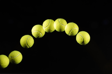 Movement or bounce of tennis ball isolated on black background.