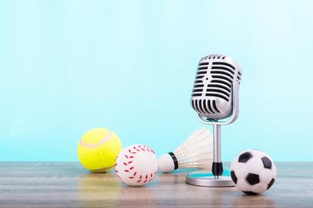 Comentarista deportivo de concepto: el micrófono retro puesto en la mesa de madera con fútbol o fútbol, pelota de tenis, béisbol y volante aislado sobre fondo azul