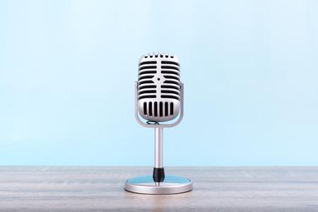 Micrófono retro Poner sobre mesa de madera aislada sobre fondo azul.