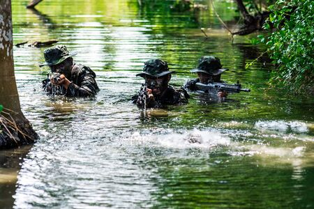 Bangkok Thailand - April 21 , 2018 : Simulation of the battle plan. Three military officers rose up out of the water to attack the enemy. Photo rally by Nikon Club Thailand at 11Th Infantry Regiment.