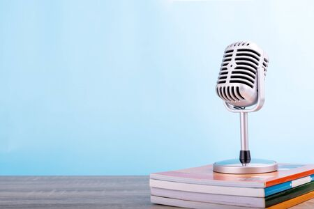 Education teaching concept : Retro microphone with many book put on wooden table isolated on blue background. Stock Photo