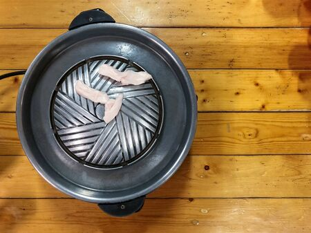 Korean Barbecue in Thai Style Food : Top view of Black electric pan with lard pork put on wooden table Stok Fotoğraf