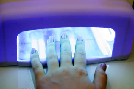 UV lamp gel polish manicure process in a beauty salon. Salon procedure. The master coats the client's nails with a varnish.