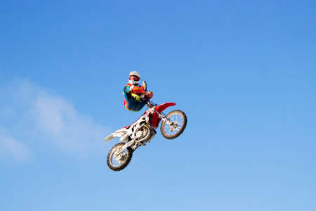 Biker on a motorcycle doing tricks in the air. Blue sky in the background.